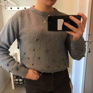 Ljusblå tröja med grå/silvet pärlor Färgen är ljusare än vad som syns på bilden Fraktkostnaden tillkommer