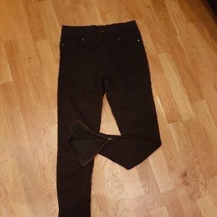 Svarta byxor med dragkedja längst ner på benen.