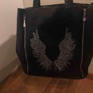 Snygg handväska med vingar på, några diamanter har lossnat. Går att justera storleken lite på väskan tack vare dragkedjorna som finns både fram och bak.