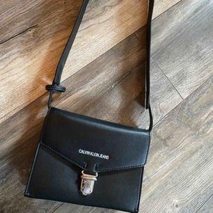 Säljer calvin klein envelope bag i svart med blå insida, kan användas som både axelremsväska samt midjeväska. Inköpt på nelly.se 2019.  Köparen betalar frakt.   H20 W14 D4 CM