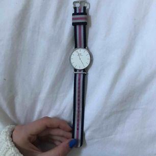 Säljer min äkta Daniel Wellington klocka! Silver klocka med ett rosa,blått och vitt band som dock är smutsigt på två ställen, men annars väldigt bra skick! Nypris 1399kr! Köparen står för frakten!