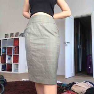Skitsnygg grönrutig kjol som går över knäna. Kjolen är insydd så att den passar en smalare midja och går ut i en M. Har inte fått användning för kjolen och är i bra skick!