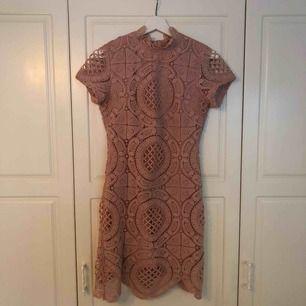 Rosa klänning med spets på yttersta lagret. Använd vid 3 tillfällen, har dock hängt ett tag i garderoben. Storlek 36, s. Köpt på Nelly.