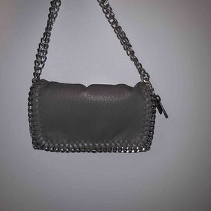 superfin grå väska! axelbandet är vikt så att man kan ha den som en kort väska runt axeln men går att göra längre! knappt använd❣️