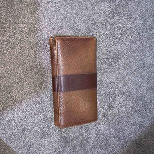 Brun plånbok som passar för 50-60 åriga kvinnor, den är i bra skick