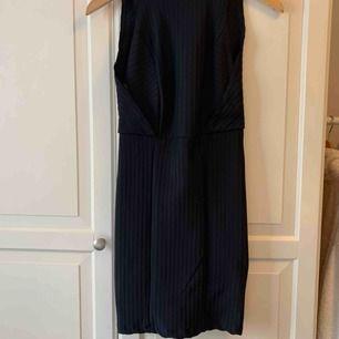 Oanvänd svart klänning med dragkedja på baksidan