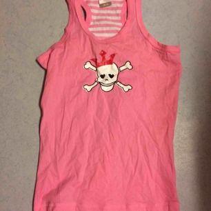 Sött rosa linne med döskalle fram. På baksidan är det rosa/vit randigt. Märkt som 146/152 men jag kunde ha det när jag var xs/s. Fint skick. Frakt: 42 kr  OBS: Tillhörande shorts finns i en annan annons :)