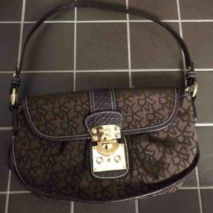 Sjukt fin väska från märket DKNY! Påminner lite om en LV väska i färg och form när han hänger den över axeln. Guld detaljer och skinn detaljer! Kan skicka men då betalar köparen för frakten :)