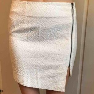 Figurnära kjol i mönstrat material, med slits. Insydd i midjan. Är i bra skick!