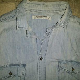 Fin jeansskjorta från Junkyards egna märke. Sitter perfekt både uppknäppt med något under eller knäppt hela vägen upp. Storlek XL.