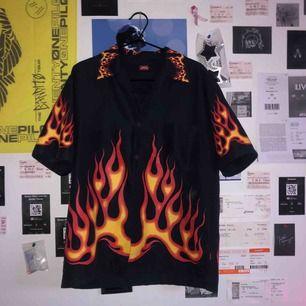 en asball mörkblå skjorta med eldflammor. köpt för ett tag sen på Plick men är fortfarande i ett otroligt bra skick! kan frakta eller mötas upp i Knivsta