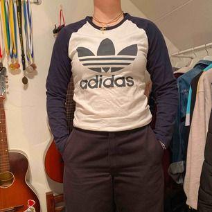 Adidas långärmad tröja med marinblått Adidasbyxor tryck på bröstet och marinblå armar. Lite urtvättad därav priset. Annars fin!! Jag brukar ha storlek M i tröjor så denna är bara lite tight på mig, alltså bra i storlek till många!
