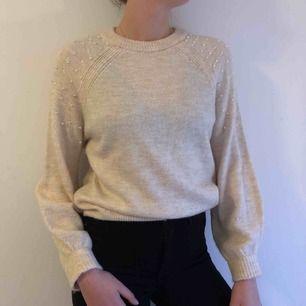 Väldigt mjuk och skön stickad tröja med fina pärlor på axlarna. Fin beige/offwhite färg.