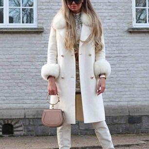 Helt ny vit kappa från borninstockholm, ÄKTA pälskrage & pälsmuddar! Färg; offwhite. Knytning i midjan om man vill, går att ta av. Avtagbar päls. Helt ny med lappar kvar! Nypris: 5800kr
