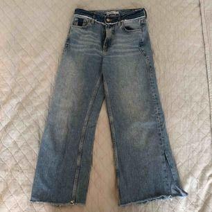 Ett par ljusblå Jeans från Zara som är lite kortare och avklippta där nertill. Det är designat som ett inbyggt bälte upptill med lite slitningar där med. Inga andra skador eller slitningar på byxorna i allmänhet. (Frakt tillkommer)