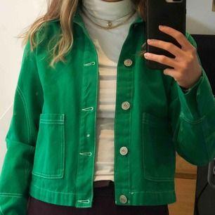 En grön jeansjacka med vita sömmar och knappar från Urban outfitters. Den har två stora fickor framtill, har inga slitningar och är i bra skick. Originalpris: 400 kr  Frakt tillkommer