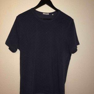 Mörkblå bläck t-shirt. Liten vit fläck på bröstet, går nog att få bort.
