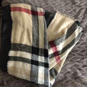 En stor scarf som är som en filt. Väldigt varm och har två mönster. Burberry märke utåt och grå inåt.