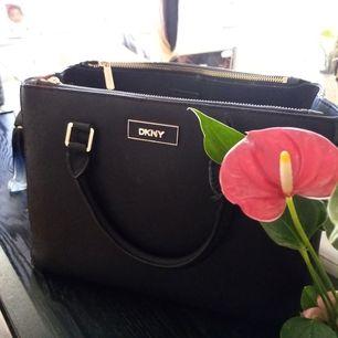En äkta DKNY väska, köpt i London.. Men används sällan. Pris kan diskuteras. Finns även axelrem till. Lagom stor med ett stor fack i mitten och två fCk på sidorna med dragkedjor och små fack där inne.. Mer bilder finns.. Hör av dig om du är intresserad.
