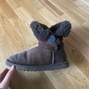 """Säljer ett par Uggs i modellen """"Bailey Burton"""". Väl använda, relativt slitna men fortfarande fina. Ett pyttelitet hål på ena skon, se andra bilden."""