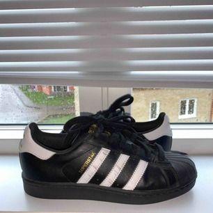 Adidas Superstar svarta. Köpta för 699kr och använda 3 ggr. Köparen står för frakten eller möts upp i Helsingborg. Nästan nyskick förutom de svarta strecken på högra skon men syns inte på långt håll. 💕