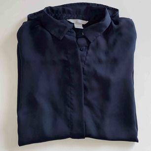 Silkesaktig skjorta från HM i marinblått. Superfint skick, då jag endast använt den en gång. Svårt att få med den bra på bild men den är superfin!