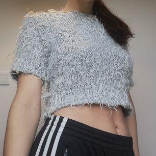 Fluffig grå magtröja med lite glitter i. Står att det är M/L men passar bra på mig med XS, stretchig så funkar på alla. Väldigt rejvig och 90s tröja. Frakt 59 kr.