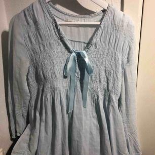 Ljusblå blus från Tessie med rosett. Stl M.  80 kr + fraktkostnad.