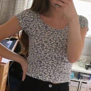 Blå vit blommig topp/t-shirt i lite kortare modell! Fint skick!  Är stretchig så kan nog passa S också!  60kr + frakt.