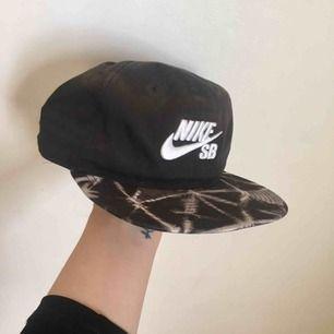 Keps från Nike med spänne i bak. I sjukt snyggt batik/stentvättade är mönster på skärmen och svart i övrigt. Sparsamt använd.