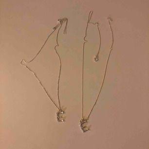 Två silverhalsband med ett E. En för 100kr, men priset kan diskuteras. Kan mötas upp i Stockholm eller swisha det går lika bra.