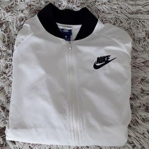 En vit nike bomber jacka. Nike märket på vänstra bröstet. I väldigt bra skick. Kan få en bra oversize look till dom med storlek s/m.