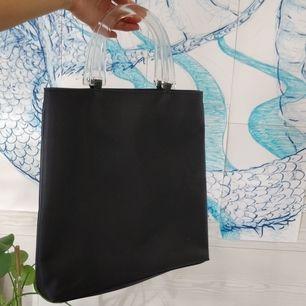 Y2k svart handväska med genomskinliga handtag. Köptes på secondhand och kommer tyvärr inte till användning. Jättebra skick. (Frakt ingår)