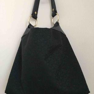 Rymlig dkny väska i begagnat skick. Tråden har gått upp vid ringarna på handtaget men får lätt att sy för den som orkar eller lämna till skräddare därav det låga priset. Väskan är äkta (köpt på NK i Sthlm).