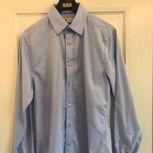 Snygg blå slim fit skjorta från Riley. Storleken är Small. Fraktkostnad tillkommer.