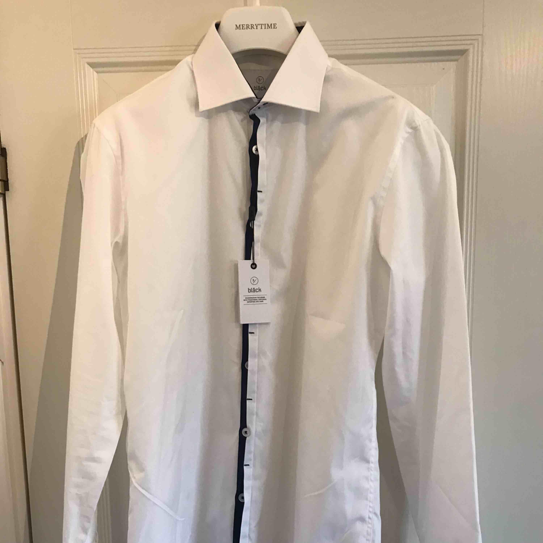 Helt oanvänd snygg vit skjorta från Bläck. 100% bomull och tvättas i 40 grader. Halva priset gentemot nypris. Jag har inte använt skjortan då jag lagt undan den i garderoben och sedan glömt bort den, nu har jag växt ut den. Fraktkostnad tillkommer.. Skjortor.