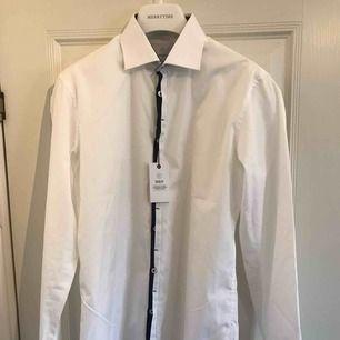 Helt oanvänd snygg vit skjorta från Bläck. 100% bomull och tvättas i 40 grader. Halva priset gentemot nypris. Jag har inte använt skjortan då jag lagt undan den i garderoben och sedan glömt bort den, nu har jag växt ut den. Fraktkostnad tillkommer.
