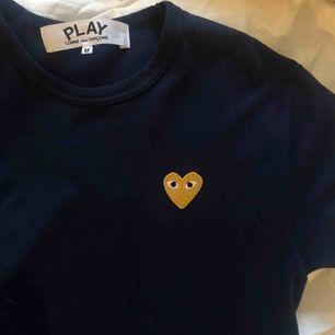 Comme des Garcons t-shirt i marinblått med guldiga hjärta i storlek M! (funkar för både killar och tjejer) Använts 2 gånger, därför jag säljer den för att den inte kommer till användning. Finns inga hål, slitningar eller fläckar. Nypris 900 kr