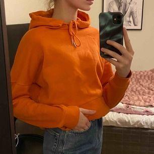 En orange hoodie med knytning. Använd 2 gånger och köptes för 300