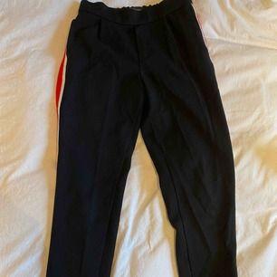 Storlek: S Svarta kostymbyxor med rödvit rand på bägge sidorna❤️🤍 Inte använda mycket☺️ Haft ett tag därav priset💸