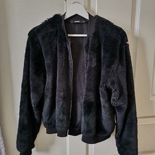 En jacka/tröja i fluffigt svart material