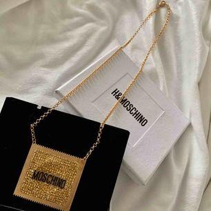 Helt Ny och Unik Moschino halsband från H&M i samarbete med Moschino i form av en kondom. De har tillverkats i begränsad antal så det är definitivt en unik exemplar.  Size of pendant 5.5x6 cm. Length of necklace 66 cm.
