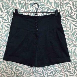 Svarta högmidjade shorts i sailorstil. Snygga med instoppad randig top tex!   Använda men jättefint skick! Från Vila, storlek xs, passar xs/s.