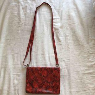 Röd ormskinns väska från Monki. Går att ställa bandet och rymms med en del. 50kr + frakt 💖