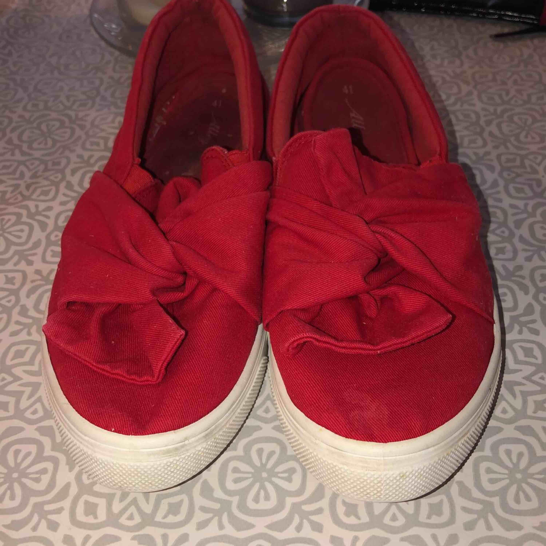 röda skor, knyten framtill som detalj . Skor.