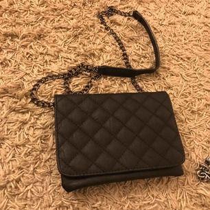 Oanvänd väska med svart kedja