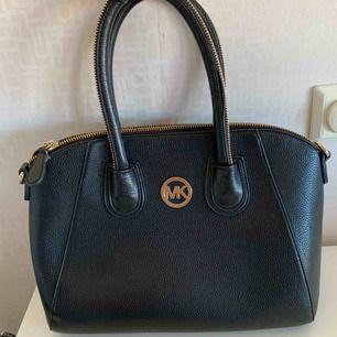 Fin väska i svart med gulddetaljer. MK, fått den i present, kan ej garantera äkthet. Ser exklusiv och dyr ut. Mellantor modell, rymmer mycket. Elegant och stilren modell. Skickas eller hämtas i centrala Göteborg.