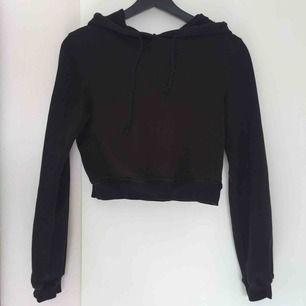 """En svart croppad hoodie från Nelly.com i modellen """"Cropped Sweat Hoodie"""". Använd 2-3 gånger så den är i mycket fint skick. Orginalpris 299kr."""