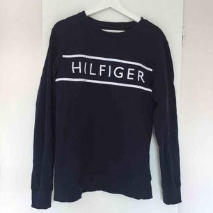 En marinblå sweatshirt från Tommy Hilfiger i storlek 176. Den är använd ca 4 gånger, men bara hemma så den är i fint skick. Orginalpris ca 799kr.