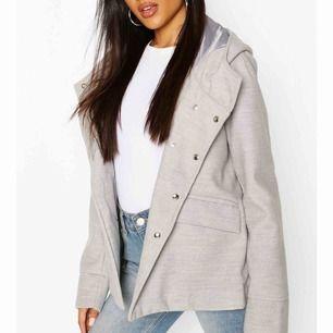 En helt ny grå kappa med luva prislappen kvar! Ull liknande material.